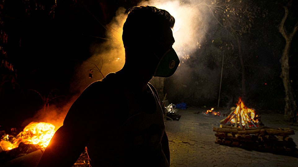 Ramananda Sarkar, 43, who has cremated more than 450 COVID-19 victims stands by burning funeral pyres of COVID-19 victims in Gauhati, India