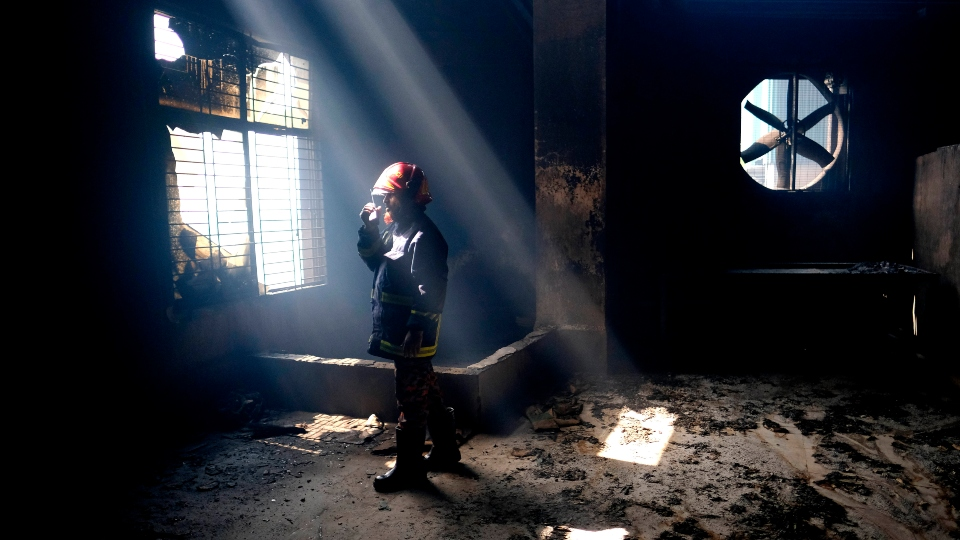 A firefighter communicates with his colleagues on a walkie talkie inside the burnt food and beverage factory in Rupganj, outside Dhaka, Bangladesh, Friday, July 9, 2021.