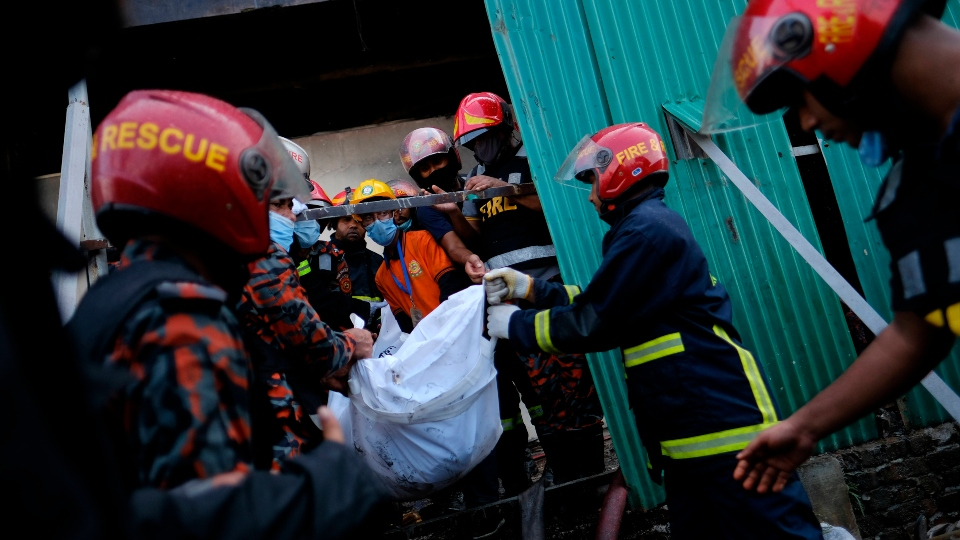 Firefighters carry the body of a victim at a food and beverage factory in Rupganj, outside Dhaka, Bangladesh, Friday, July 9, 2021.
