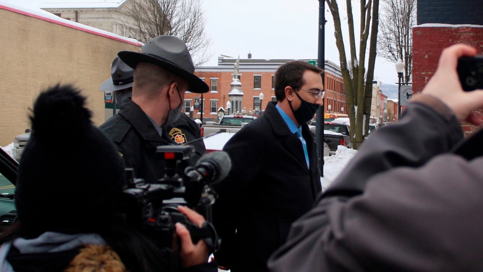 In this Feb. 3, 2021 file photo, Bradford County, Pa., District Attorney Chad Salsman is escorted into Magisterial District Court, in Towanda, Pa.