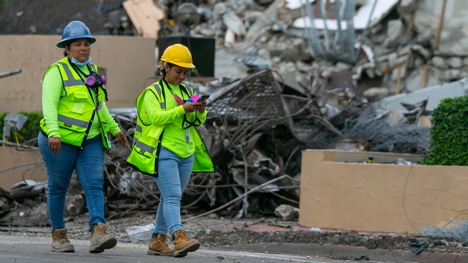 A workers make her way past the rubble and debris of the Champlain Towers South condo in Surfside, Florida on Tuesday, July 6, 2021.