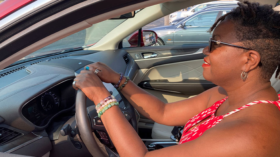 Jessica Pitts sits behind the wheel of a 2019 Lincoln MKC on the lot of Jack Demmer Lincoln in Dearborn, Mich., on Monday, July 19, 2021.