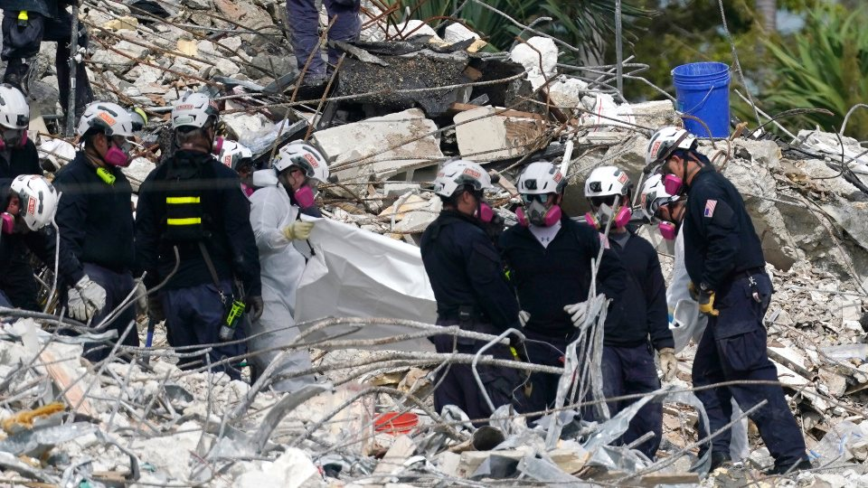 Rescue workers use a tarp for recovered remains at the site of the collapsed Champlain Towers South condo building, Monday, July 5, 2021 in Surfside, Fla. The remaining structure was demolished Sunday, which partially collapsed June 24. Many people remain unaccounted for. (AP Photo/Lynne Sladky)