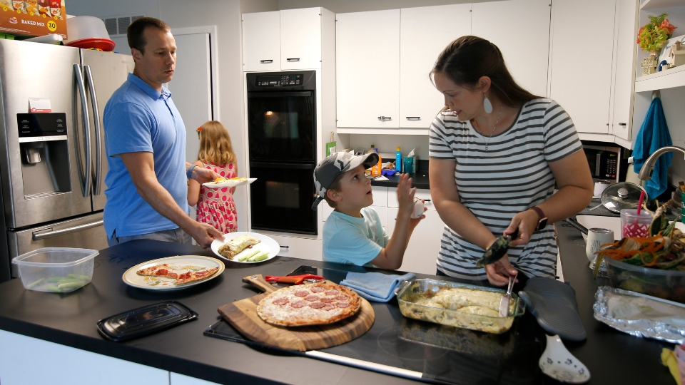 Chris and Kristen Umphlett prepare dinner with two of their four children, Kyria, 9, rear, and Derek 7, Wednesday, June 30, 2021, in their home in East Lansing, Mich. The Umphletts have fostered unaccompanied migrant children during the pandemic. (AP Photo/Al Goldis)
