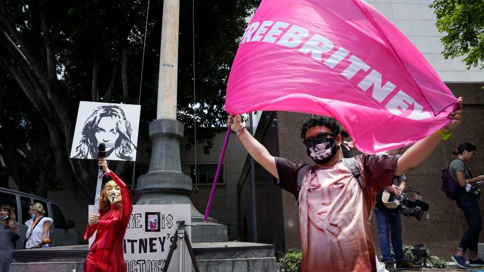 Britney Spears supporters Gabriela Ruiz, left, and Carlos Morales demonstrate outside a court hearing concerning the pop singer's conservatorship at the Stanley Mosk Courthouse, Wednesday, June 23, 2021, in Los Angeles.