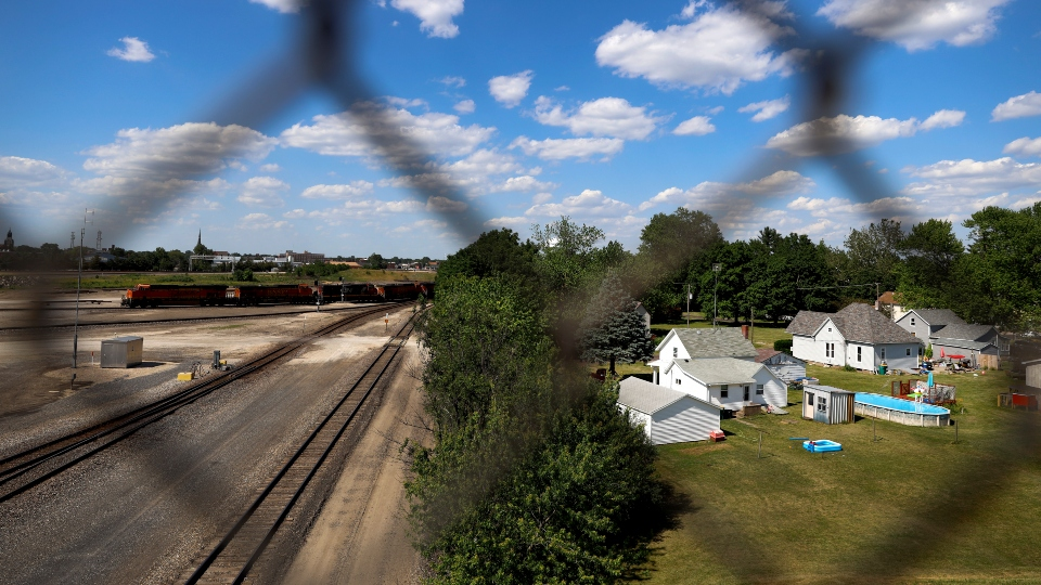 A freight train yard is separated from a neighborhood by a row of trees, Tuesday, June 15, 2021, in Galesburg, Ill. Settled more than 180 years ago, Galesburg was built around Knox College, founded by Presbyterians from upstate New York seeking a Christian school on the western frontier. The city soon became home to Illinois' first anti-slavery society. (AP Photo/Shafkat Anowar)