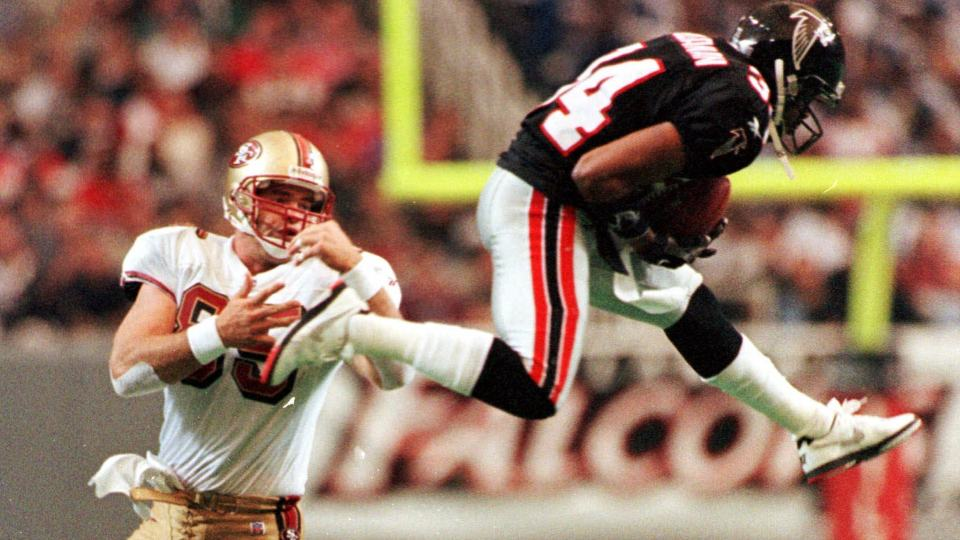 Atlanta Falcons Ray Buchanan (34) intercepts a Steve Young pass intended for San Francisco 49ers tight end Greg Clark (85) during second half play in Atlanta Sunday, Nov. 15, 1998. Buchanan returned the ball to the one yard line to set up a Falcons touchdown. (AP Photo/John Bazemore)