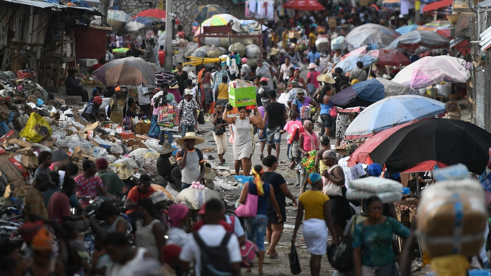 A woman carries a basin with her belongings at the Petion-Ville market in Port-au-Prince, Haiti, Sunday, July 11, 2021, four days after the assassination of Haitian President Jovenel Moise.