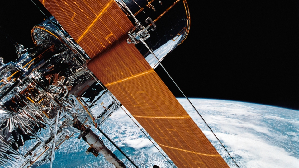 In this April 25, 1990 photograph provided by NASA, most of the giant Hubble Space Telescope can be seen as it is suspended in space by Discovery's Remote Manipulator System (RMS) following the deployment of part of its solar panels and antennae.