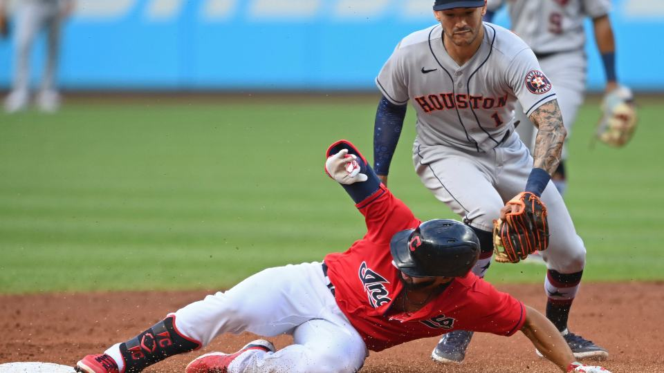 Cleveland Indians' Bobby Bradley slides into second for a double next to Houston Astros' Carlos Correa (1) during the first inning of a baseball game, Saturday, July 3, 2021, in Cleveland. (AP Photo/David Dermer)