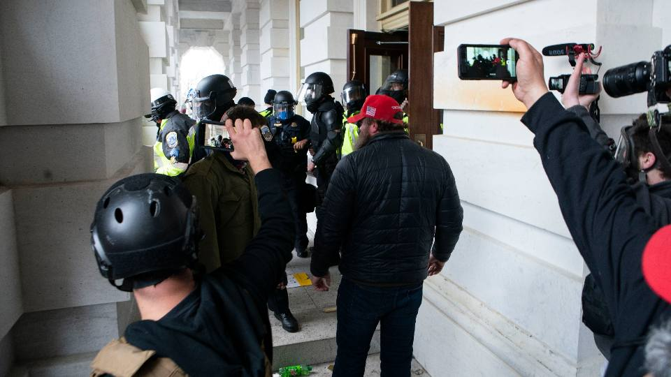 In this Jan. 6, 2021, file photo people record as Capitol police officers push back violent insurrectionists loyal to President Donald Trump U.S. Capitol in Washington.