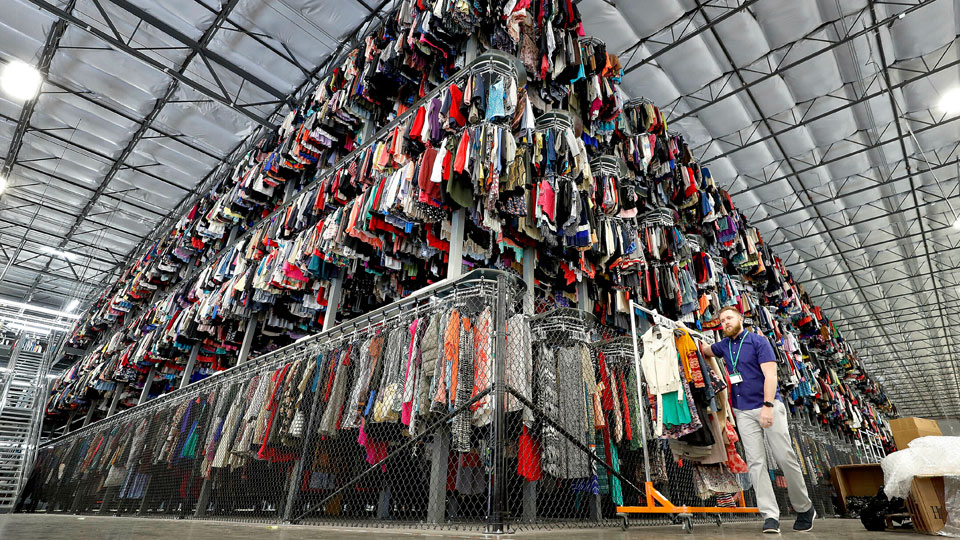 Thousands of garments are stored on a three-tiered conveyor system at the ThredUp sorting facility in Phoenix on March 12, 2019