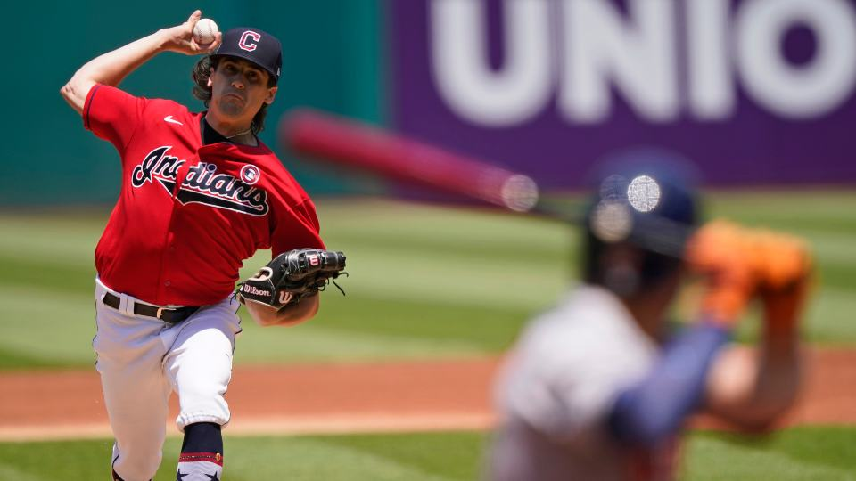 Cleveland Indians starting pitcher Cal Quantrill, left, delivers to Houston Astros' Jose Altuve in the first inning of a baseball game, Sunday, July 4, 2021, in Cleveland. (AP Photo/Tony Dejak)