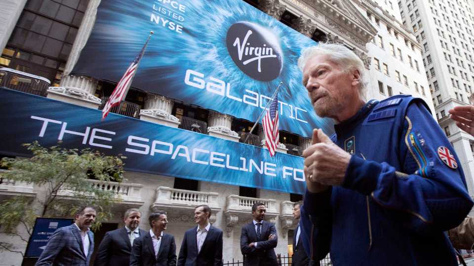 FILE - In this Monday, Oct. 28, 2019 file photo, Richard Branson, right, founder of Virgin Galactic, and company executives gather for photos outside the New York Stock Exchange before his company's IPO. Branson announced Thursday, July 1, 2021 he plans to fly into space this month on the next test flight of his Virgin Galactic rocket ship. The launch window will open July 11.