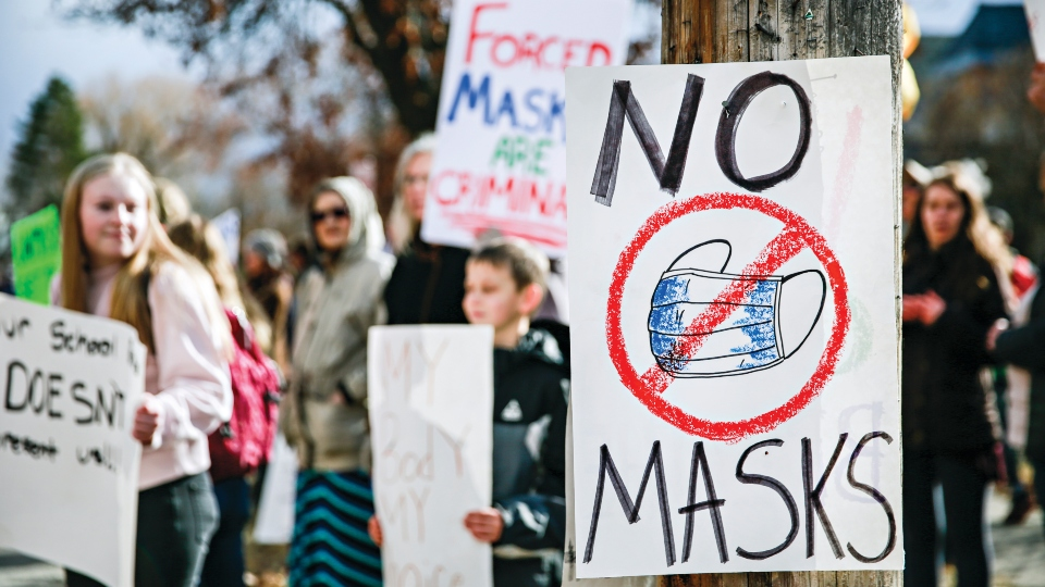 Demonstrators gather outside Flathead High School to protest the Kalispell School District's face mask requirement on March 9, 2021, in Kalispell, Mont.