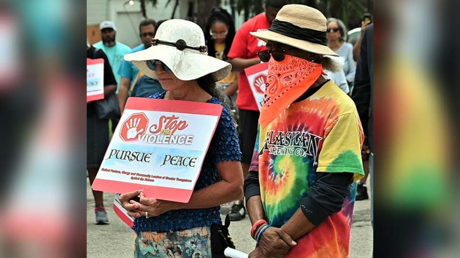 Two of the participants in the Stop The Violence Prayer Walk Saturday pause to pray on Sherwood Avenue on the South Side. (WKBN Photo/Joe Gorman)