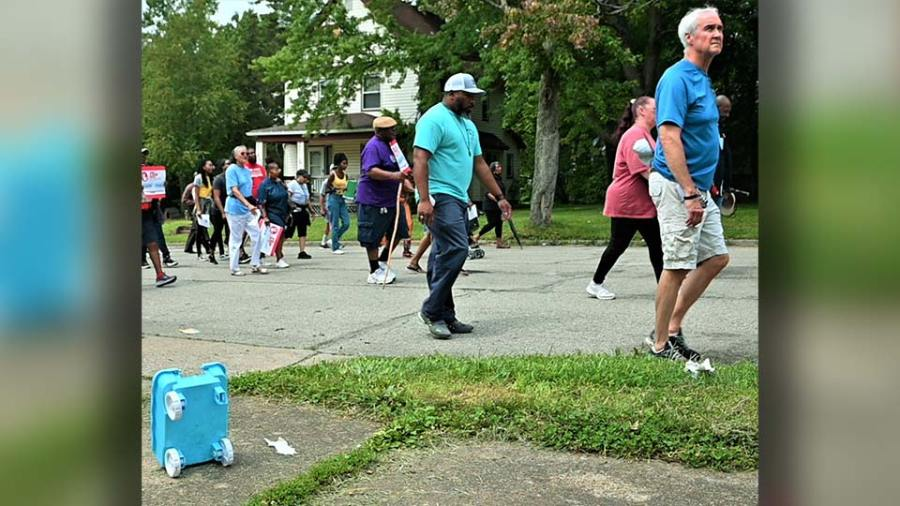 Marchers in the Prayer Walk To Stop The Violence Saturday on the South Side of Youngstown walk past some childrens toys on Sherwood Avenue. (WKBN Photo/Joe Gorman)