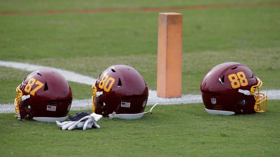 In this June 2, 2021, file photo, Washington Football Team helmets are on the field during an NFL football OTA at Inova Sports Performance Center in Ashburn, Va.