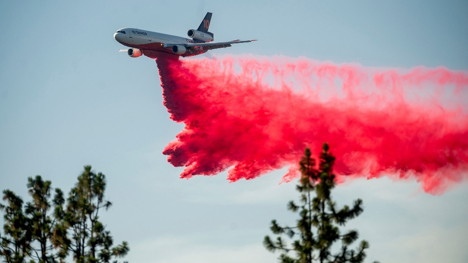 In this July 2, 2021, file photo a DC-10 air tanker drops retardant while battling the Salt Fire near the Lakehead community of Unincorporated Shasta County, Calif.