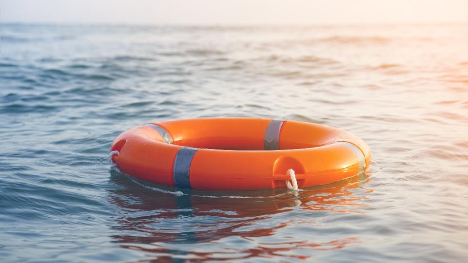 Orange lifebuoy in sea on water