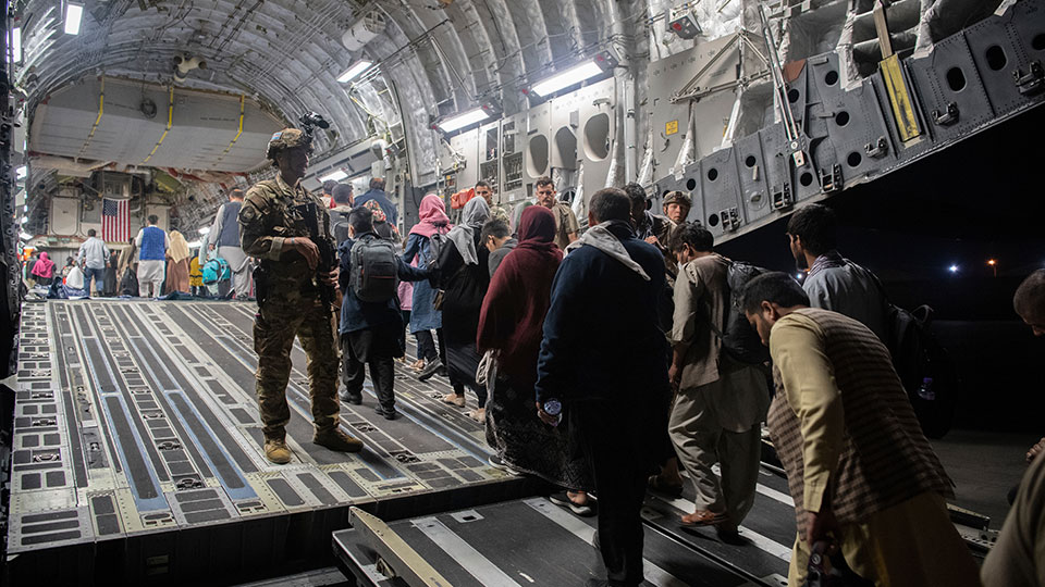 U.S. Air Force, Afghan passengers board a U.S. Air Force C-17 Globemaster III during the Afghanistan evacuation at Hamid Karzai International Airport in Kabul, Afghanistan