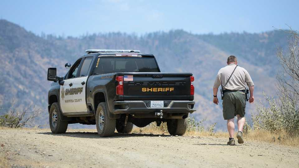 A Mariposa County deputy sheriff stands watch over a remote area northeast of the town of Mariposa, Calif., on Wednesday, Aug. 18, 2021, near the area where a family and their dog were reportedly found dead the day before. Investigators are considering whether toxic algae blooms or other hazards may have contributed to the deaths of the Northern California couple, their baby and the family dog on a remote hiking trail, authorities said.