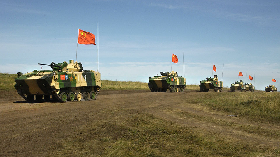 Chinese APCs roll by during a rehearsal for a massive joint military exercise by the two former Cold War rivals