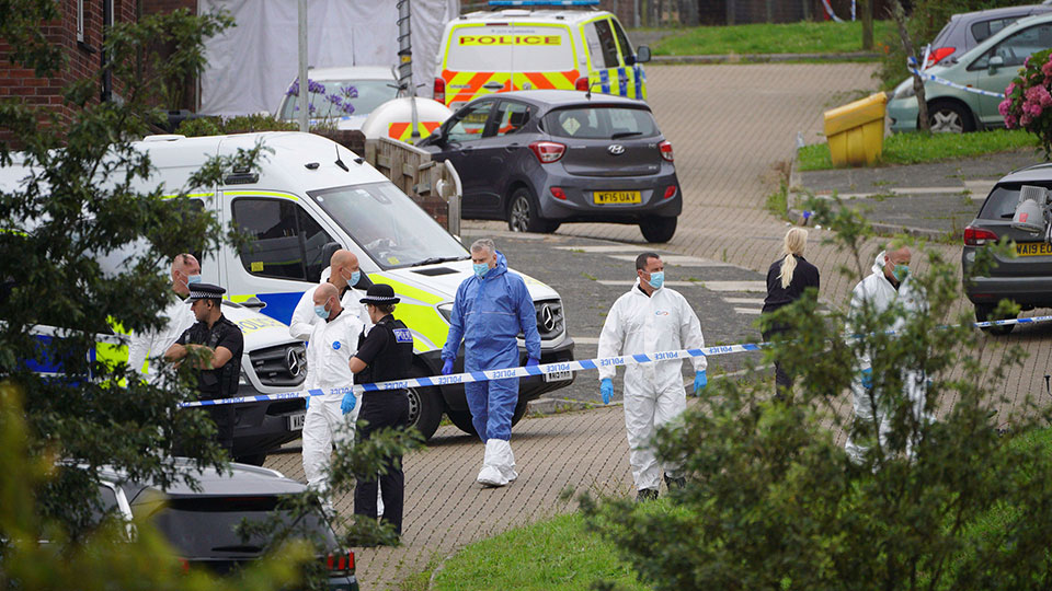 Forensic officers walk in Biddick Drive in the Keyham area of Plymouth, England Friday Aug. 13, 2021