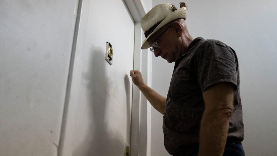 """Gary Zaremba knocks on an apartment door as he checks in with tenants to discuss building maintenance at one of his at properties, Thursday, Aug. 12, 2021, in the Queens borough of New York. Landlords say they have suffered financially due to various state, local and federal moratoriums in place since last year. """"Without rent, we're out of business,"""" said Zaremba. (AP Photo/John Minchillo)"""