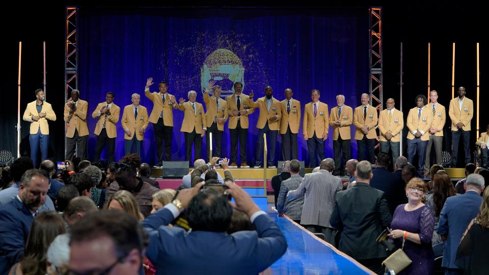 The members of both the Pro Football Hall of Fame Class of 2021, and the Centennial Class line up on stage after receiving their gold jackets during the gold jacket dinner in Canton, Ohio, Friday, Aug. 6, 2021 (AP Photo/Gene J. Puskar)
