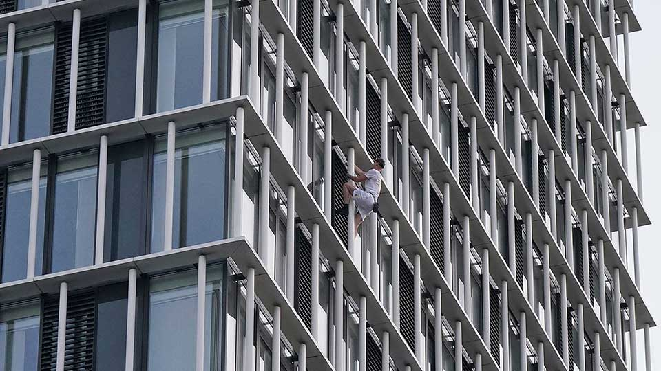 Free-solo climber George King climbs the Stratosphere Tower building, a 36-story residential tower block in Stratford, east London Tuesday, Aug. 3, 2021