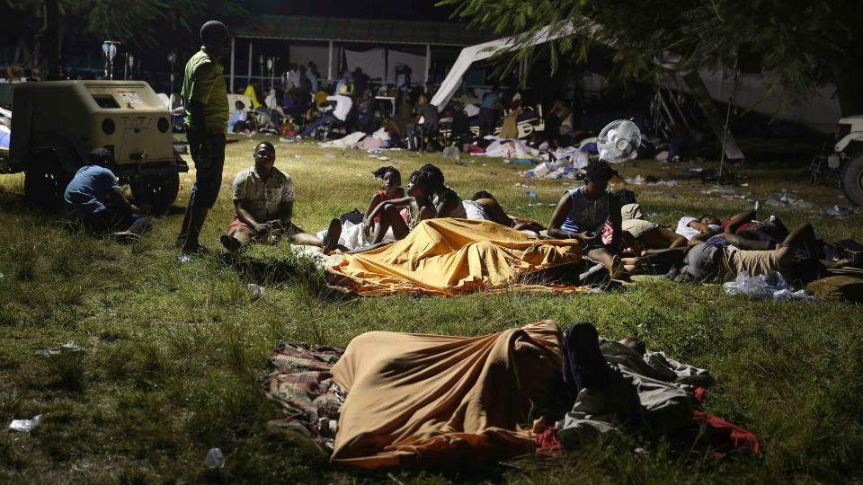 People displaced from their earthquake destroyed homes spend the night outdoors in a grassy area that is part of a hospital in Les Cayes, Haiti, late Saturday, Aug. 14, 2021. A powerful magnitude 7.2 earthquake struck southwestern Haiti on Saturday. (AP Photo/Joseph Odelyn)