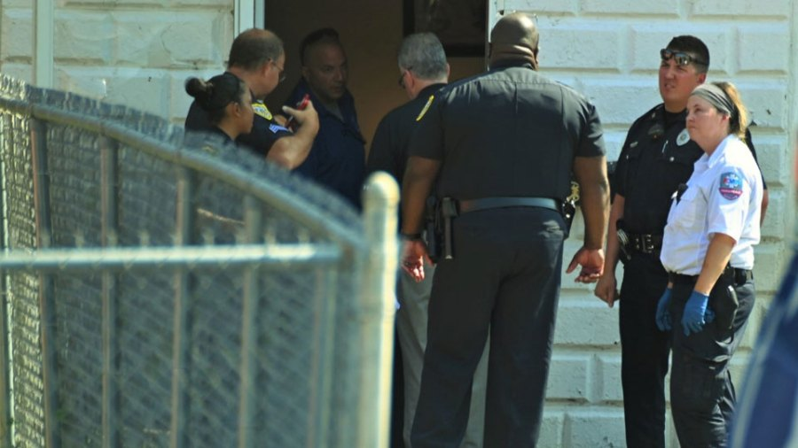 Detectives, police and paramedics Tuesday confer at the front of a home behind a Salt Springs Road building where a woman was killed and a man wounded in a shooting just after 10 a.m.