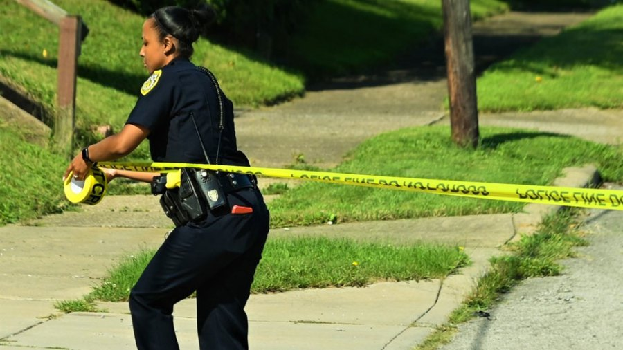 Youngstown police officer Jennifer Hudson tapes off the crime scene Tuesday on Salt Springs Road where a woman was killed and a man wounded