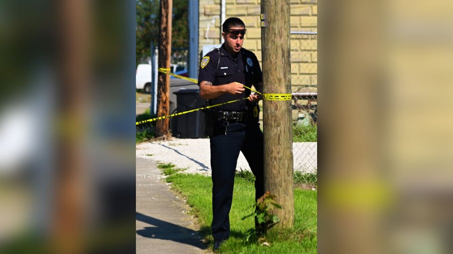 Youngstown police officer Christopher Weibel Tuesday tapes off the crime scene on Salt Springs Road where a woman was killed and a man wounded following a shooting