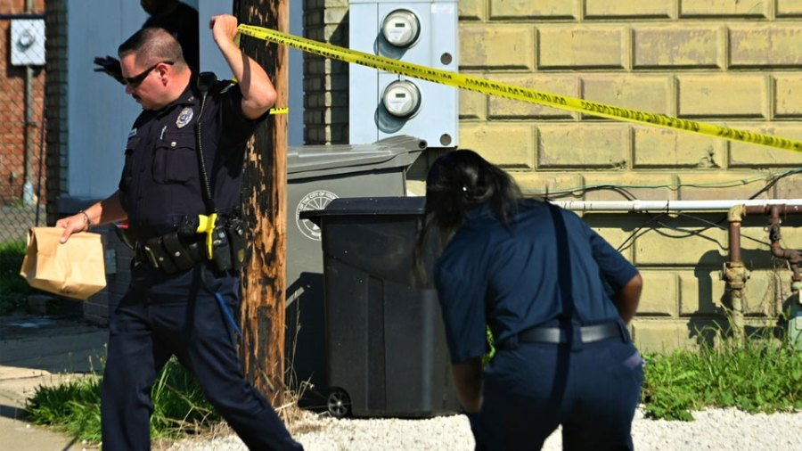 Youngstown police officer Joe Moran, left, carries a bag with evidence inside as a paramedic with American Medical Response ducks under the crime scene Tuesday after a double shooting in the 1200 block of Salt Springs Road that left a woman dead and a man injured