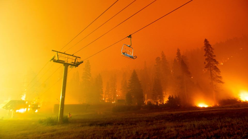 Seen in a long camera exposure, the Caldor Fire burns at the Sierra-at-Tahoe ski resort on Sunday, Aug. 29, 2021, in Eldorado National Forest, Calif. The main buildings at the ski slope's base survived as the main fire front passed. (AP Photo/Noah Berger)