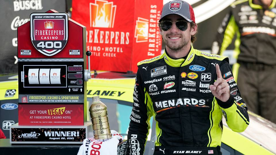 Ryan Blaney stands next to the winner's trophy after the NASCAR Cup Series auto race at Michigan International Speedway, Sunday, Aug. 22, 2021, in Brooklyn, Mich.