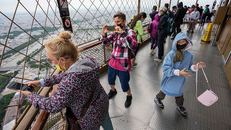 Visitors enjoy the view from top of the Eiffel Tower in Paris. The European Union is expected to recommend that its member states reinstate restrictions on tourists from the U.S. because of rising coronavirus infection levels in the country, EU diplomats said Monday, Aug. 30