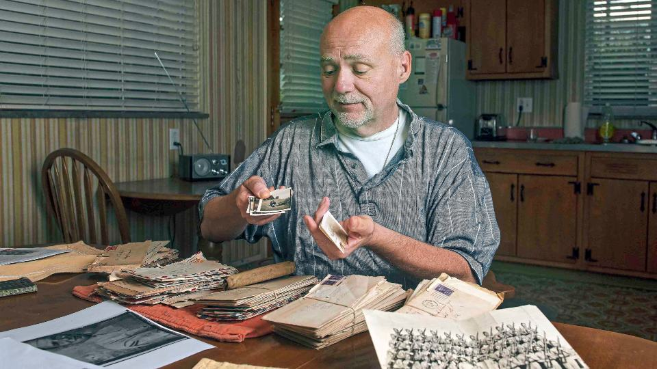 David Wassel, an attorney from White Oak, look at old letters Wednesday, Aug. 11, 2021, that Harry Dininger sent to his mother Grace Dininger while he was servicing in the Pacific Theatre during World War II. (Pittsburgh Post-Gazette via AP)