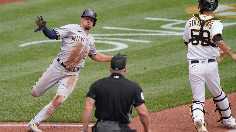 Milwaukee Brewers' Willy Adames, left, takes a wide turn to home as Pittsburgh Pirates catcher Jacob Stallings, right, looks for the throw from right fielder Gregory Polanco on a double by Brewers' Christian Yelich in the third inning of a baseball game, Sunday, Aug. 15, 2021, in Pittsburgh. The Brewers won 2-1.