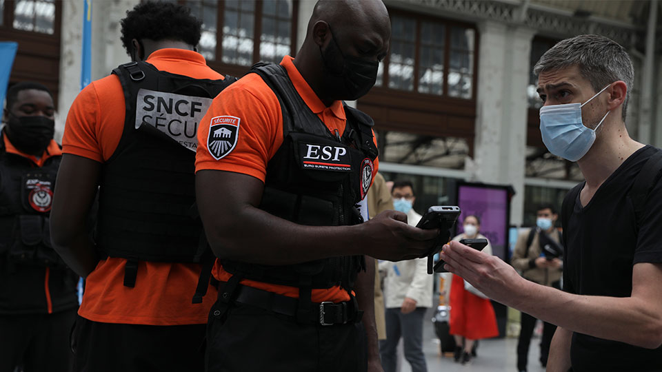 Security officers check passengers' health passes at the Gare de Lyon train station in Paris Monday Aug.9, 2021