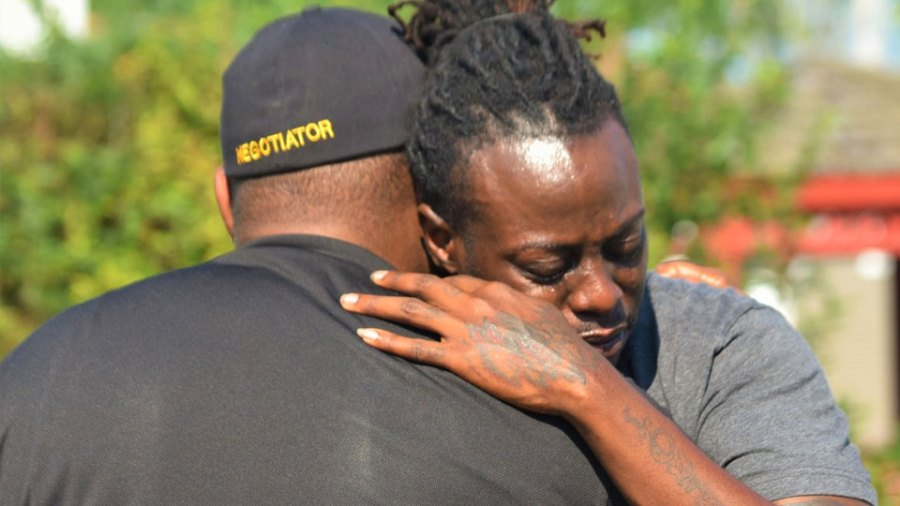 One of the relatives of the two people shot and killed Tuesday on Salt Springs Road hugs Youngstown police officer Malik Mostella Wednesday on North Bon Air Avenue, after the Mahoning Valley Crisis Response Team helped police take a car into evidence they say was used in the homicide. Mostella is a negotiator for the CRT team and coached the man here when the man ran track.