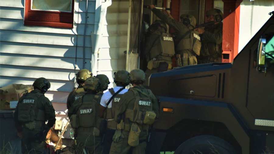 Members of the Mahoning Valley Crisis Response Team Wednesday enter a home on North Bon Air Avenue searching for the suspect in a double homicide Tuesday on Salt Springs Road. The suspect was not there