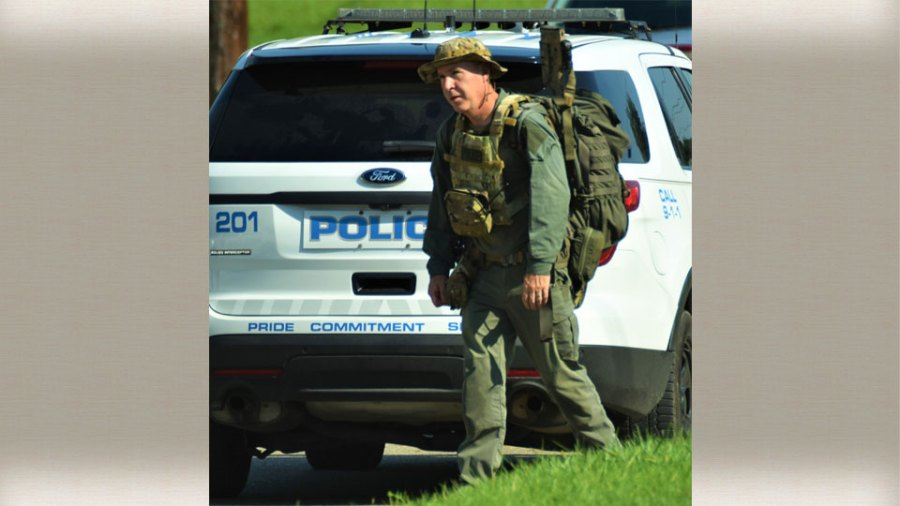 A member of the Mahoning Valley Crisis Response Team Wednesday shows the strain of lugging a lot of gear on a very hot day after they were called out to a home on North Bon Air Avenue to help police search for a murder suspect. The suspect was not there.