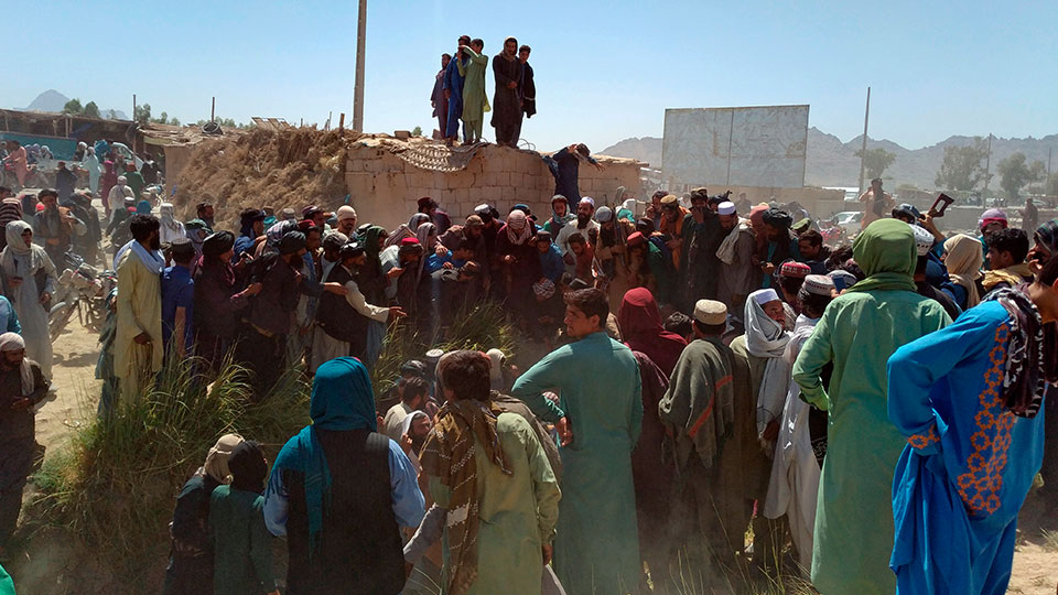 Taliban fighters and Afghans gather around the body of a member of the security forces who was killed, inside the city of Farah, capital of Farah province, southwest Afghanistan, Wednesday, Aug. 11, 2021