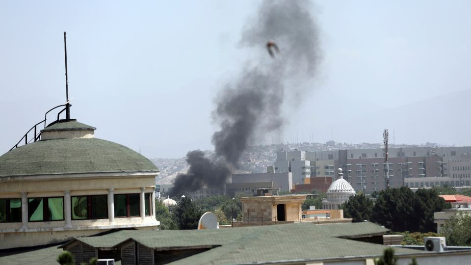 Smoke rises next to the U.S. Embassy in Kabul, Afghanistan, Sunday, Aug. 15, 2021. Taliban fighters entered the outskirts of the Afghan capital on Sunday, further tightening their grip on the country as panicked workers fled government offices and helicopters landed at the embassy. Wisps of smoke could be seen near the embassy's roof as diplomats urgently destroyed sensitive documents, according to two American military officials. (AP Photo/Rahmat Gul)