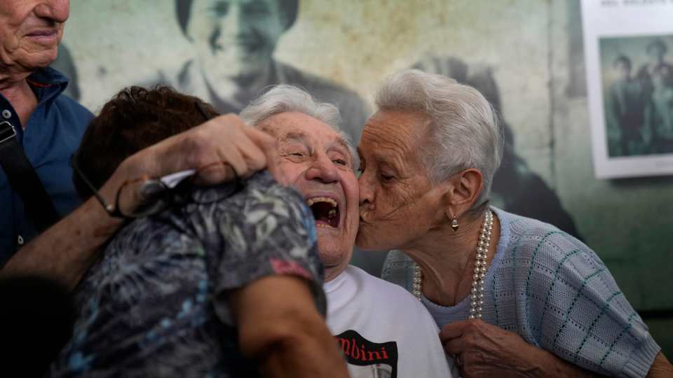 A 97 year old retired American soldier Martin Adler, center, receives a kiss by Mafalda, right, and Giuliana Naldi that he saved during a WWII, at Bologna's airport, Italy, Monday, Aug. 23, 2021. For more than seven decades, Martin Adler treasured a back-and-white photo of himself as a young soldier with a broad smile with three impeccably dressed Italian children he is credited with saving as the Nazis retreated northward in 1944. The 97-year-old World War II veteran met the three siblings -- now octogenarians themselves -- in person for the first time on Monday, eight months after a video reunion.