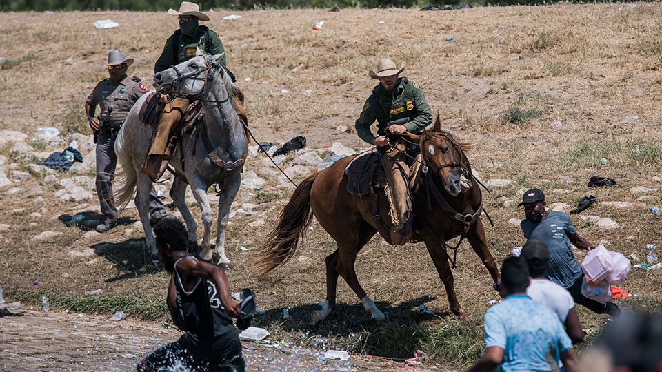 U.S. Customs and Border Protection mounted officers attempt to contain migrants as they cross the Rio Grande from Ciudad Acuña, Mexico, into Del Rio, Texas, Sunday, Sept. 19, 2021
