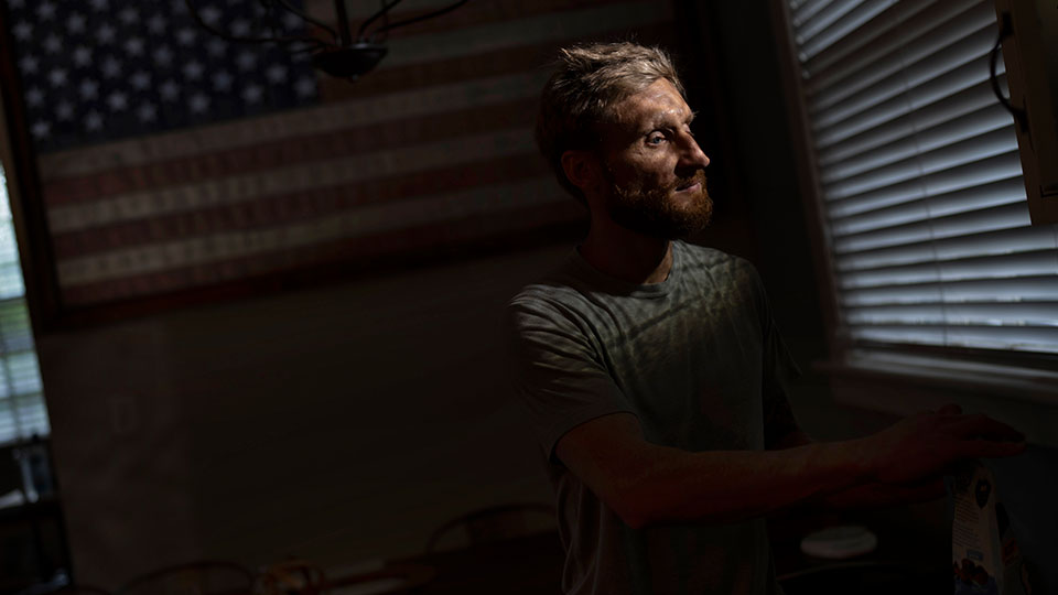 Brad Snyder prepares tea for his wife in their kitchen decorated with a flag handcrafted by Brooklyn firefighters using recycled firehose, in Princeton, N.J., on Wednesday, Aug. 4, 2021
